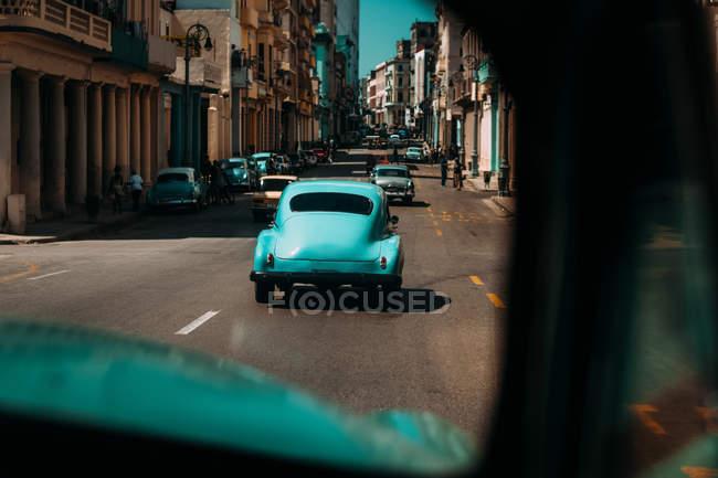 Старомодный автомобили на дороге города с ветхих зданий, Куба — стоковое фото