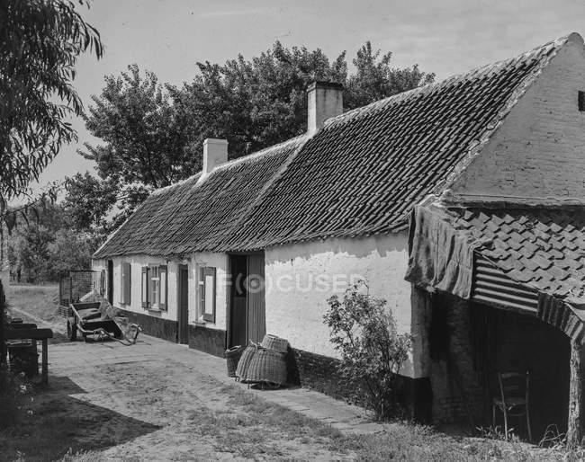 Черно-белый фасад дома с дворовыми и садовыми деревьями в деревне, Бельгия . — стоковое фото