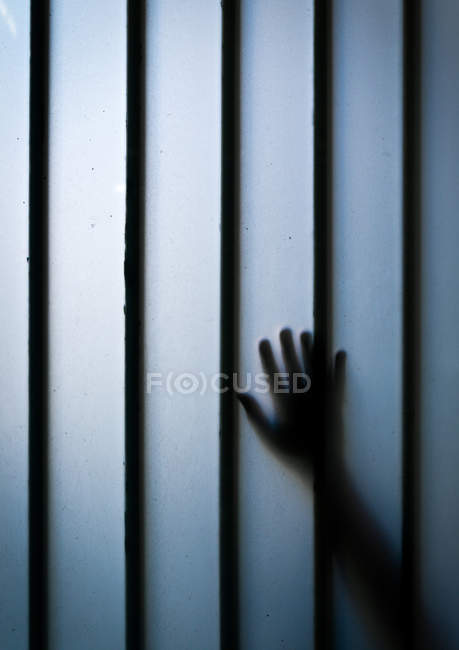 Hand touching wall with bars — Stock Photo