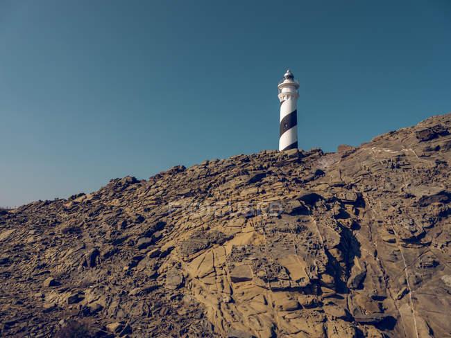Torre del faro en la colina rocosa - foto de stock