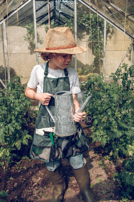 Ragazzo in piedi con irrigazione possono in serra — Foto stock