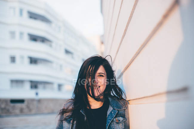 Mulher em pé na parede branca — Fotografia de Stock
