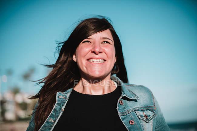 Mulher feliz em pé na frente do céu azul — Fotografia de Stock