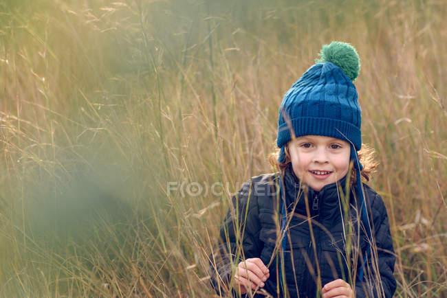 Маленький хлопчик, сидячи в траві — стокове фото