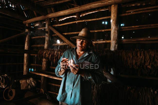 La Habana, Cuba - 1. Mai 2018: Lokale Mann Beleuchtung Zigarre unter Tabak Trocknung im Bauernhof Scheune — Stockfoto