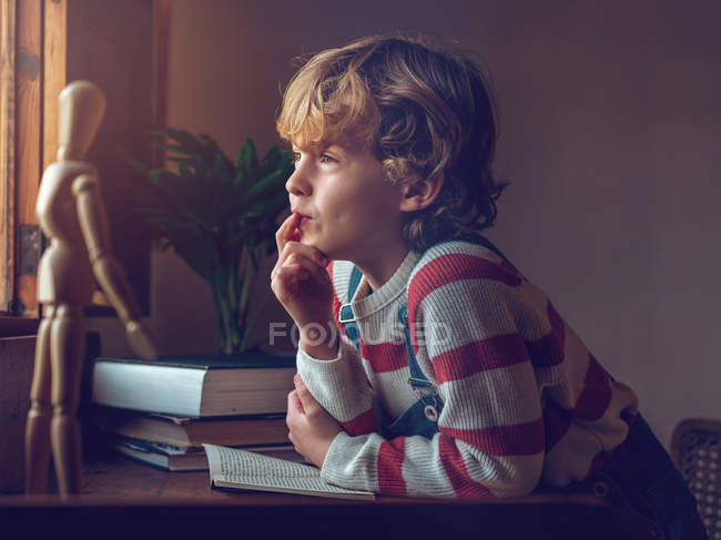 Niño sentado con libro en la mesa — Stock Photo