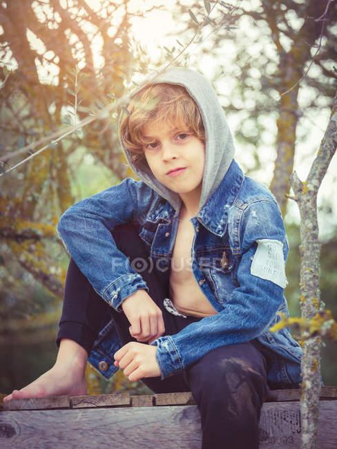 Niño sentado en el muelle de madera - foto de stock