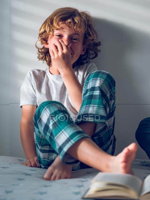Rire garçon assis sur le lit — Photo de stock