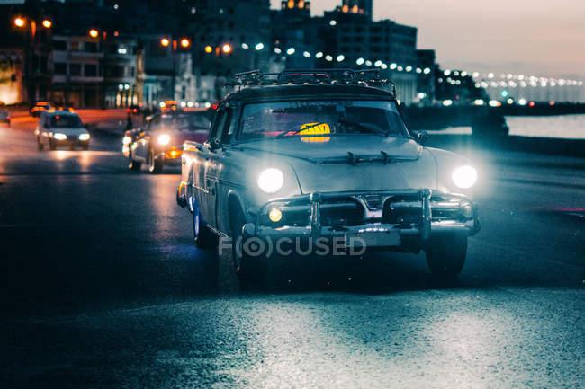 Auto d'epoca guida lungo strada in città illuminata al crepuscolo, Cuba — Foto stock