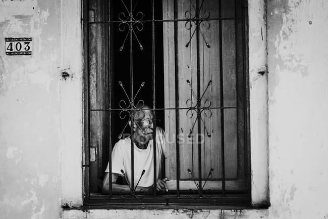 Гавана, Куба - 1 травня 2018: чорно-білий знімок літній чоловік у вікно з металевих планок, дивлячись на вулиці, Куби. — стокове фото