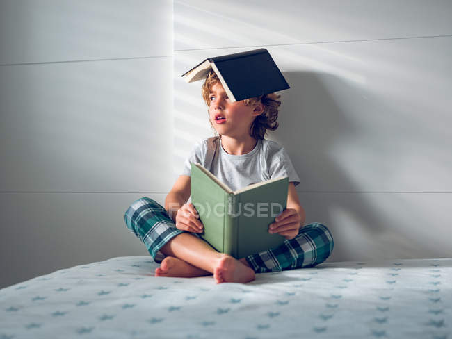 Boy with books on head and lap — Stock Photo