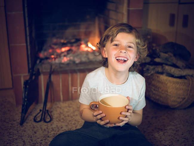 Rindo menino sentado na lareira com copo — Fotografia de Stock