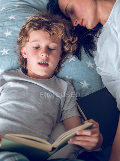 Mother sleeping and son reading book — Stock Photo