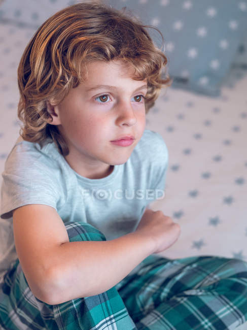 Thoughtful boy sitting on bed — Stock Photo