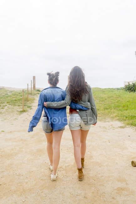 Frauen umarmen und gehen auf sandigem Pfad — Stockfoto