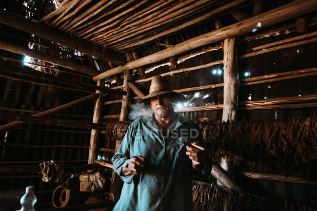 La Habana, Kuba - 1. Mai 2018: Lokale Mann halten leichter und Zigarre und suchen in der Kamera unter Tabak verlässt Trocknung im Bauernhof Scheune — Stockfoto