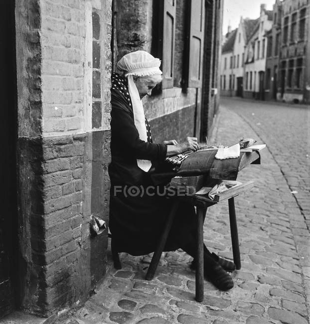 Black and white shot of senior woman sitting on street of Belgium with handcraft in leisure. — Stock Photo
