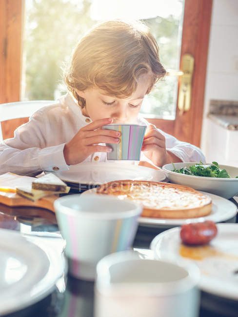 Boy drinking from cup at table — Stock Photo
