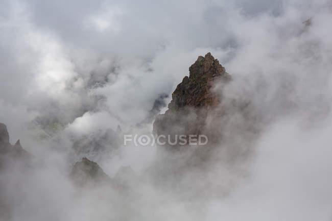 Paisaje de los picos de las montañas rocosas en nubes - foto de stock
