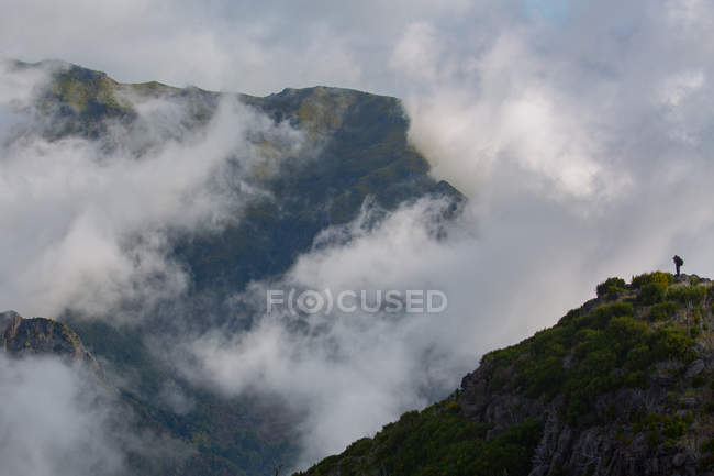 Clouds floating near peaks of high mountains — Stock Photo