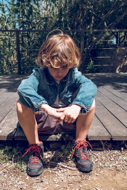 Menino bonito idade elementar com cabelo loiro encaracolado sentado na ponte de madeira e olhando para baixo na zona rural — Fotografia de Stock