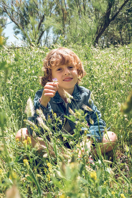 Elementary age boy sitting in wildflowers field and holding plant. — Stock Photo