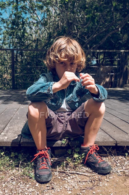 Elementary age boy with curly blond hair sitting on wooden bridge and looking in camera in countryside. — Stock Photo