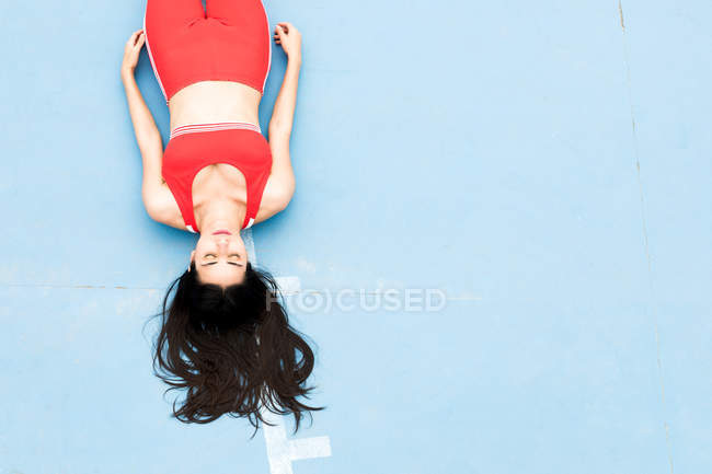 Young woman lying on sports ground — Stock Photo
