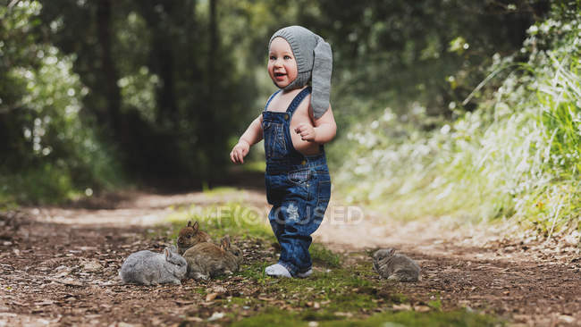 Cute little child in gray hat standing with bunnies in park — Stock Photo
