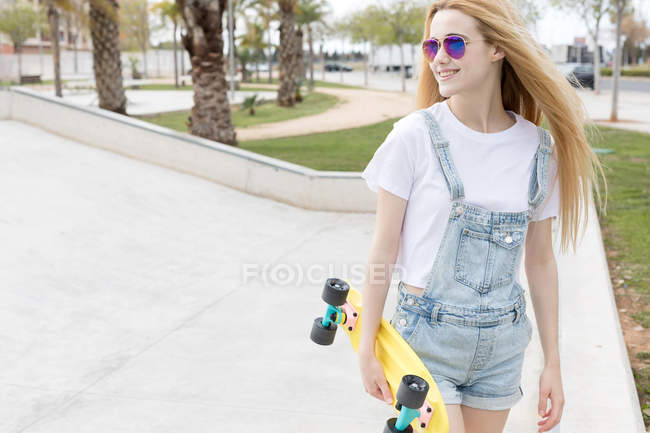 Smiling teenage girl in sunglasses and denim overalls walking with penny board in summer park — Stock Photo