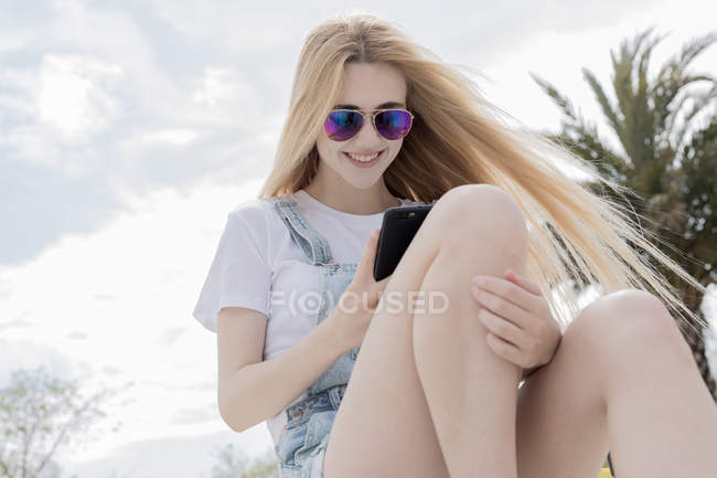 Stylish blonde teenage girl with long hair in sunglasses using smartphone and smiling — Stock Photo