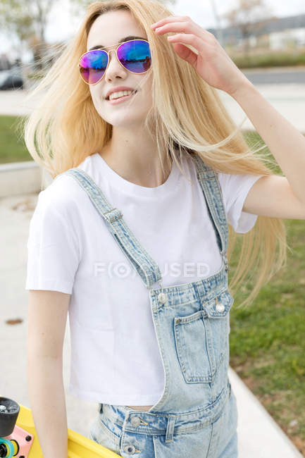 Blonde girl with penny board walking in park — Stock Photo
