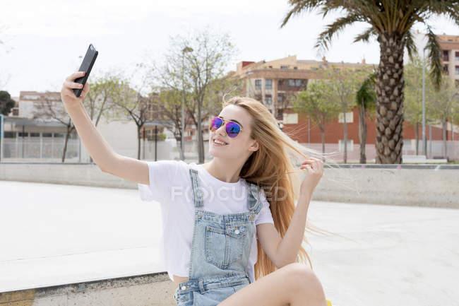 Blonde girl sitting in skate park and taking selfie — Stock Photo