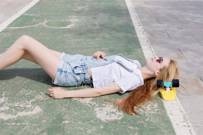 Blonde girl in sunglasses and jeans overalls lying on sidewalk with penny board under head — Stock Photo