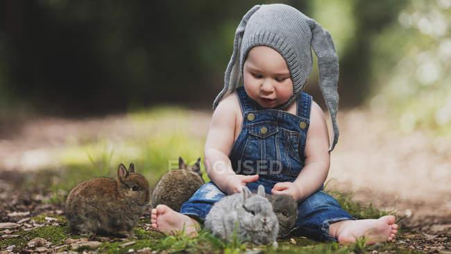 Mignon petit enfant en chapeau gris assis avec des lapins dans le parc — Photo de stock