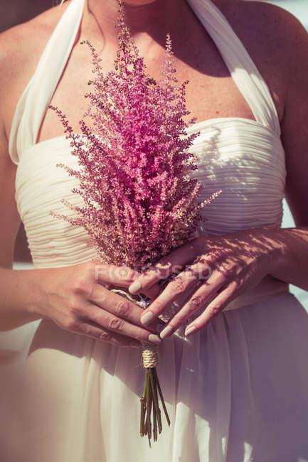 Mariée en robe festive blanche tenant le bouquet de mariée — Photo de stock