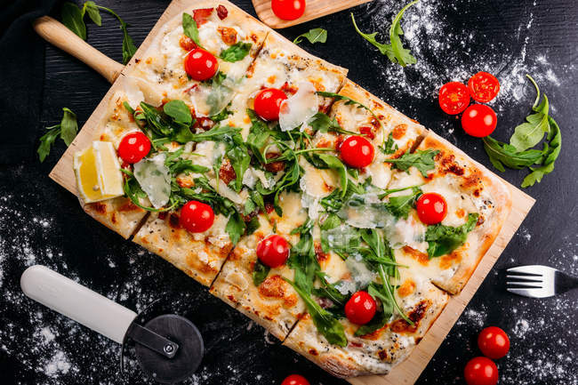 Rectangular cut pizza with cherry tomatoes, potherbs and cheese on wooden board on dark table — Stock Photo