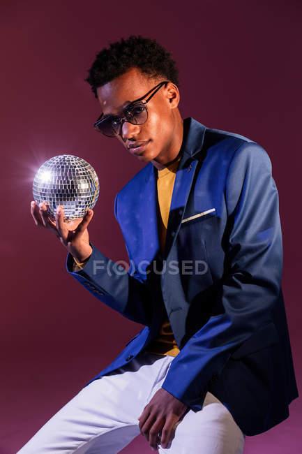 Молодой человек модный участник с диско шар на фоне тёмно фиолетовый — стоковое фото