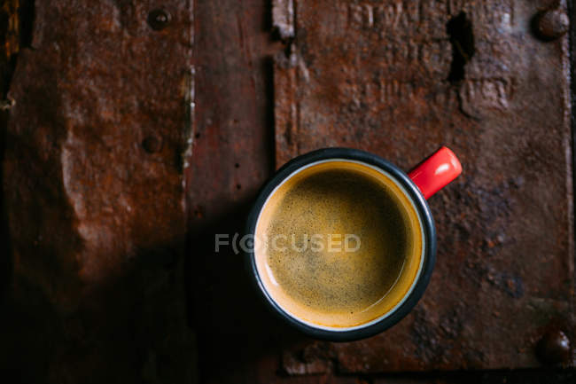 Enamel cup of coffee on rustic wooden surface — Stock Photo