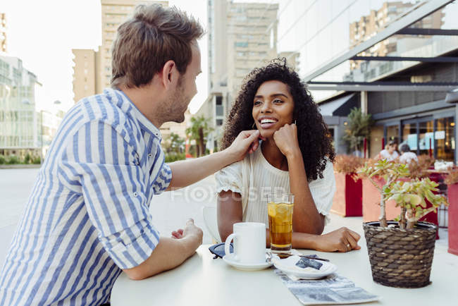 Romantic multiracial couple sitting at outdoor cafe together — Stock Photo