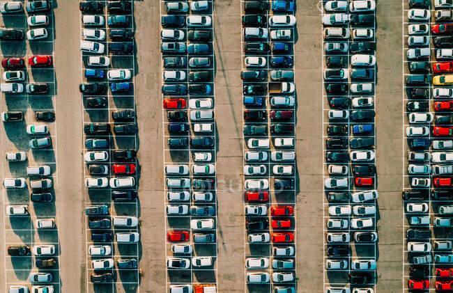 Вид с воздуха на красочные красивые автомобили, аккуратно припаркованные на старой асфальтовой поверхности в солнечный летний день — стоковое фото