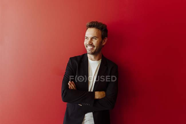 Homme souriant en tenue élégante debout sur fond rouge vif — Photo de stock