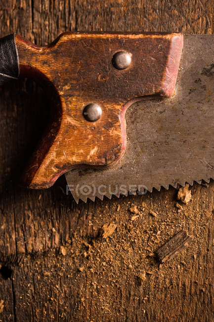Close-up of rusty handsaw on wooden surface — Stock Photo