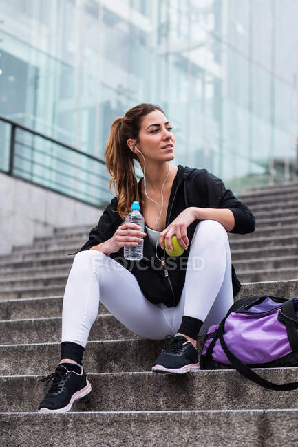 Fit woman in stylish sportswear sitting with bag on steps with apple and water — Stock Photo