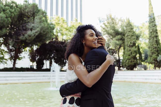 Charmant couple multiracial embrassant tout en se tenant près de la fontaine dans le parc — Photo de stock