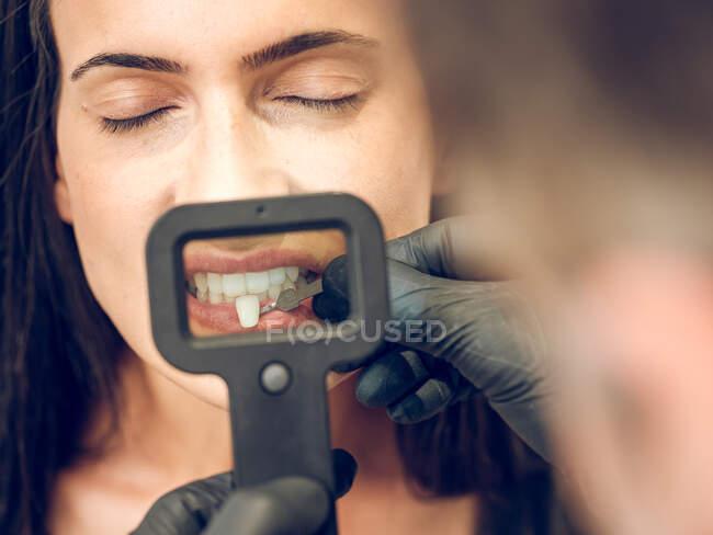 Odontólogo irreconocible recogiendo tinte de un diente para mujer sentada con los ojos cerrados - foto de stock
