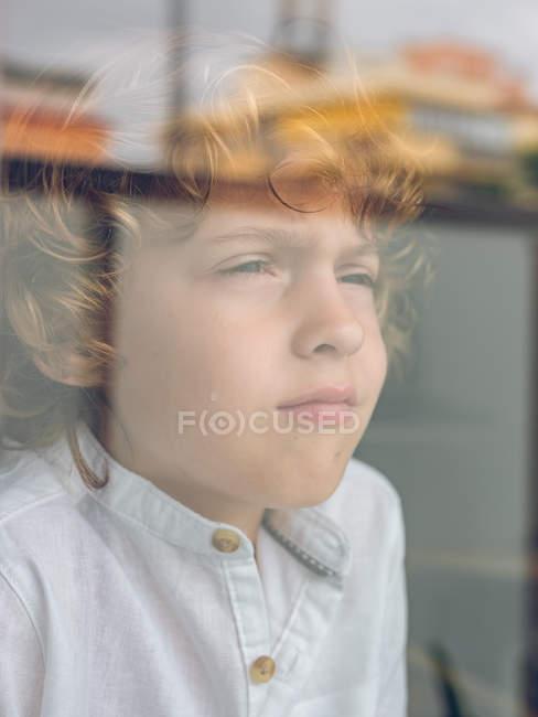 Triste niño mirando a través del vidrio - foto de stock