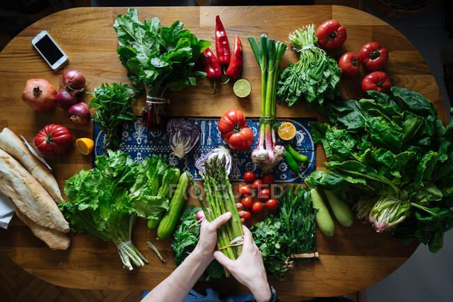 Вигляд жіночих рук з елегантного столу з свіжими здоровими овочами та інгредієнтами для приготування фруктів згори. — стокове фото