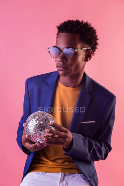 Черный человек, одетый в куртку и солнцезащитные очки, холдинг светящийся диско шар на розовом фоне — стоковое фото
