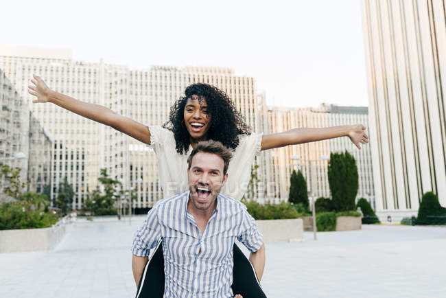 Man giving piggyback ride to African-American woman while having fun on city street together — Stock Photo